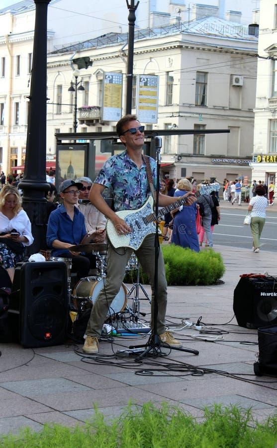 O músico da rua canta e joga na rua foto de stock