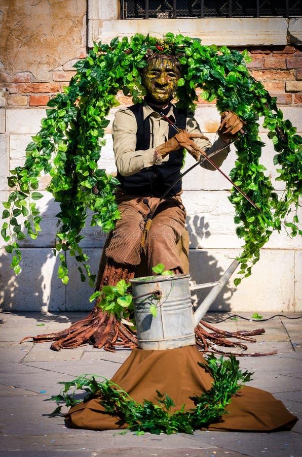 O músico disfarçado como a árvore mante distraído turistas em Veneza fotos de stock royalty free