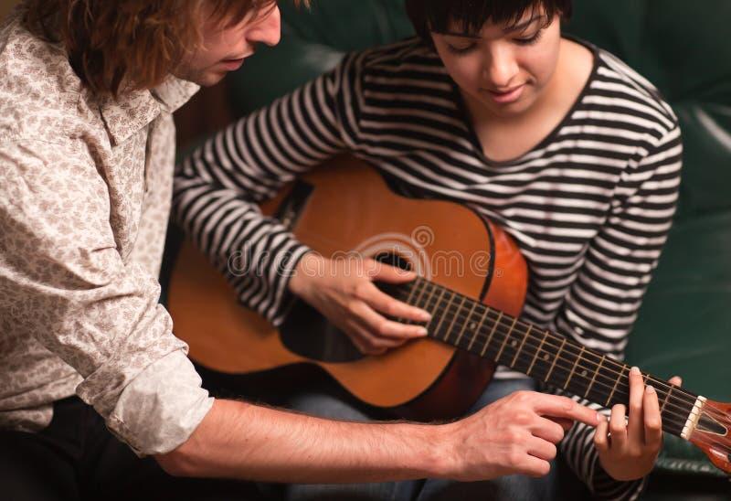 O músico ensina o estudante fêmea jogar o Guita foto de stock royalty free
