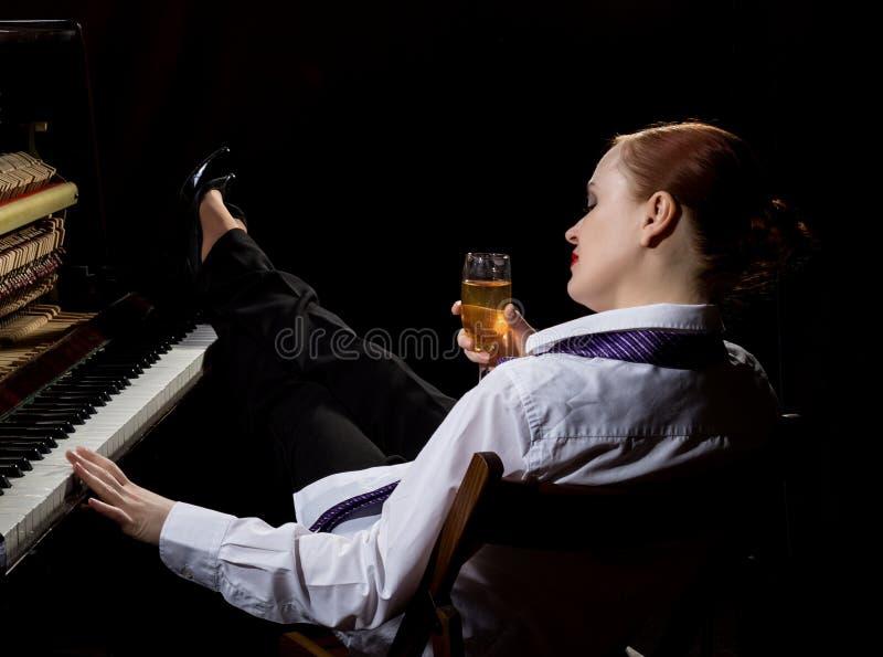 O músico fêmea vestiu-se em um terno do ` s do homem que senta-se ao lado do piano e bebe o champanhe fotografia de stock