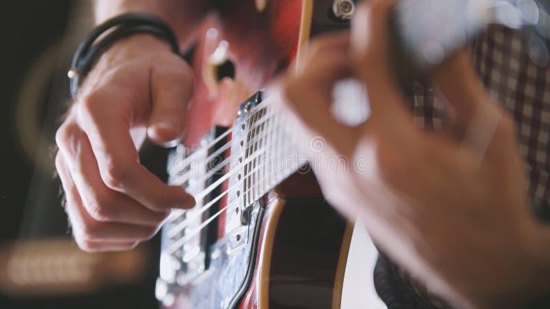 O músico masculino joga a guitarra, mãos perto acima, foco no fretboard da guitarra foto de stock