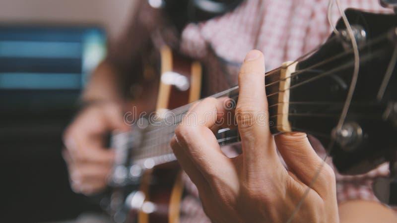 O músico masculino joga a guitarra, mãos perto acima, foco no fretboard da guitarra imagem de stock royalty free