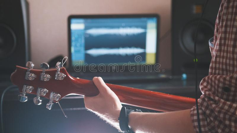 O músico masculino joga a guitarra, mãos perto acima, foco no fretboard da guitarra imagens de stock royalty free