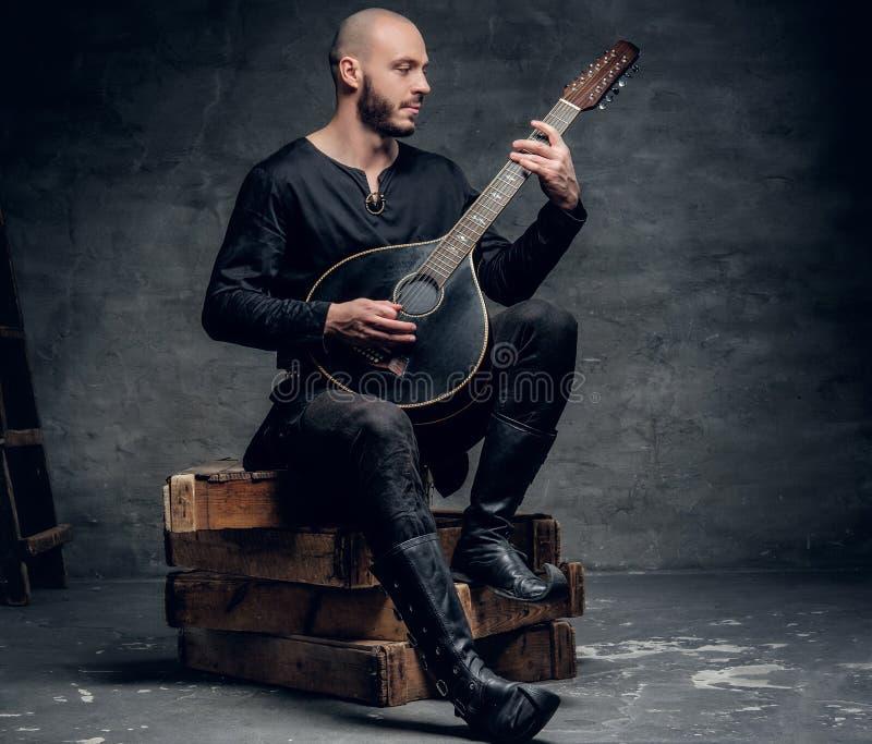 O músico popular tradicional vestido na roupa celta do vintage senta-se em uma caixa de madeira e joga-se o bandolim imagens de stock royalty free
