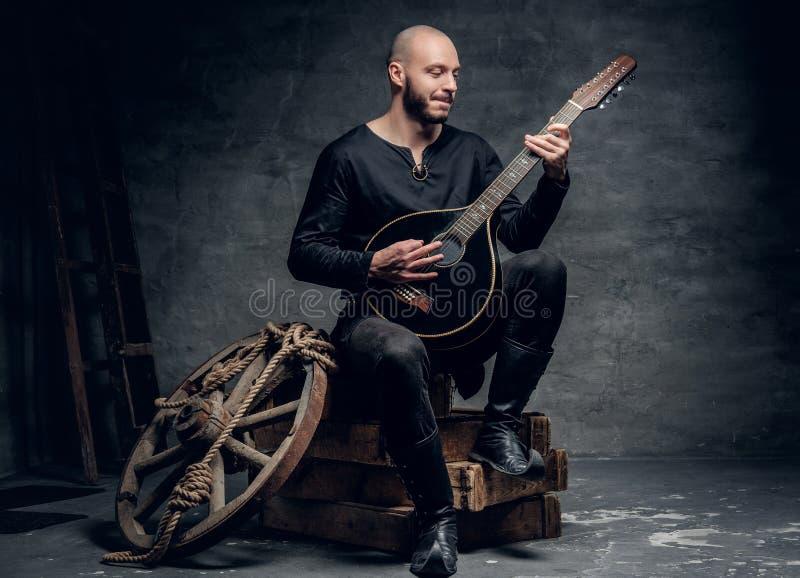O músico popular tradicional vestido na roupa celta do vintage senta-se em uma caixa de madeira e joga-se o bandolim foto de stock royalty free