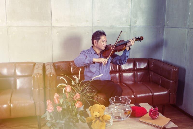 O músico que joga o violino na sala de visitas relaxa o tempo foto de stock royalty free