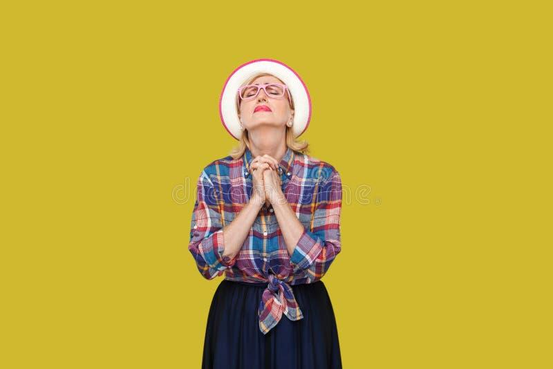 O m?j bo?e zadawala pomaga ja Portret pełny nadziei nowożytna elegancka dojrzała kobieta w przypadkowym stylu z kapeluszem, eyegl zdjęcia royalty free