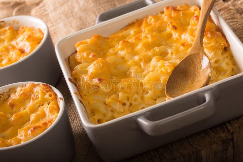 O Mac e o queijo deliciosos em um cozimento tornam côncavo o close-up em uma tabela H imagens de stock royalty free