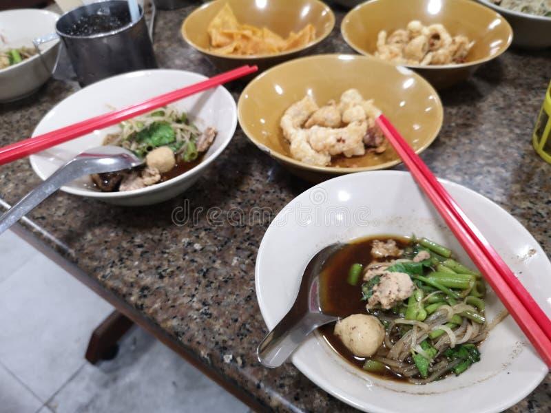 O macarronete de arroz branco do corte de multa engrossa a sopa que cobre a carne de porco e a bola cortadas da carne de porco pa imagem de stock