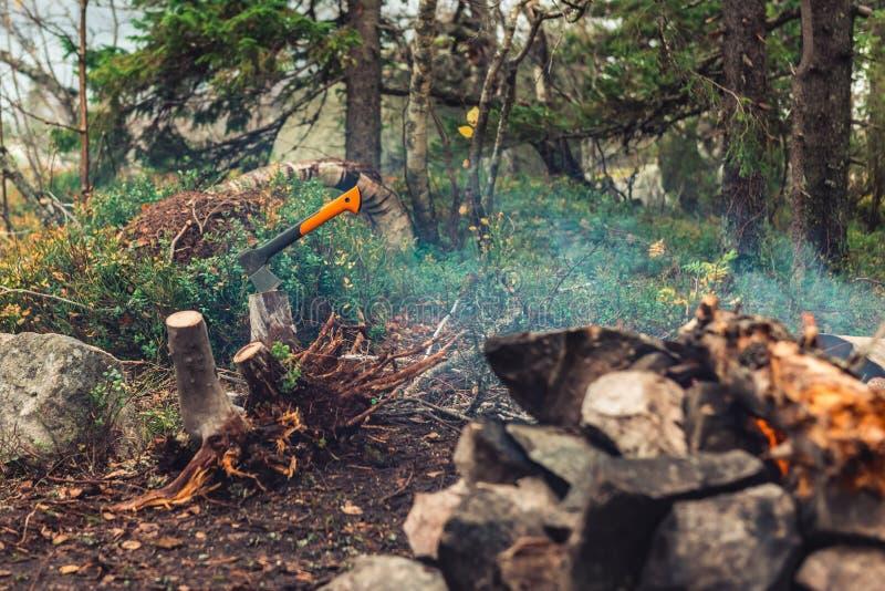 O machado colou no log perto da fogueira fotos de stock