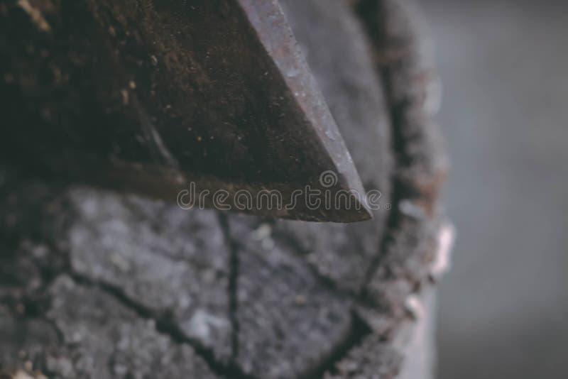 O machado velho para cortar a lenha cola para fora no coto de árvore velho Um machado afiado foi colado em um coto de madeira vel imagem de stock