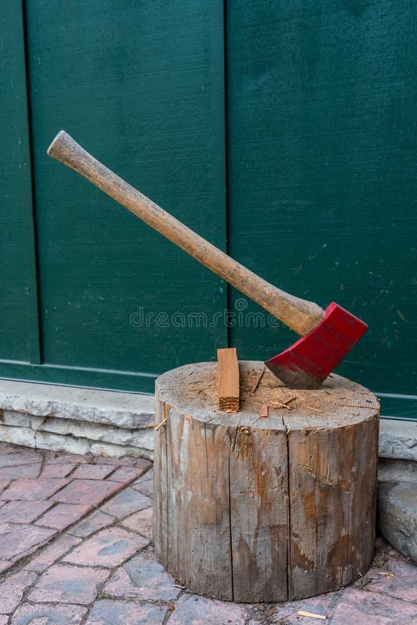 O machado vermelho e a inflamação sentam-se no log foto de stock