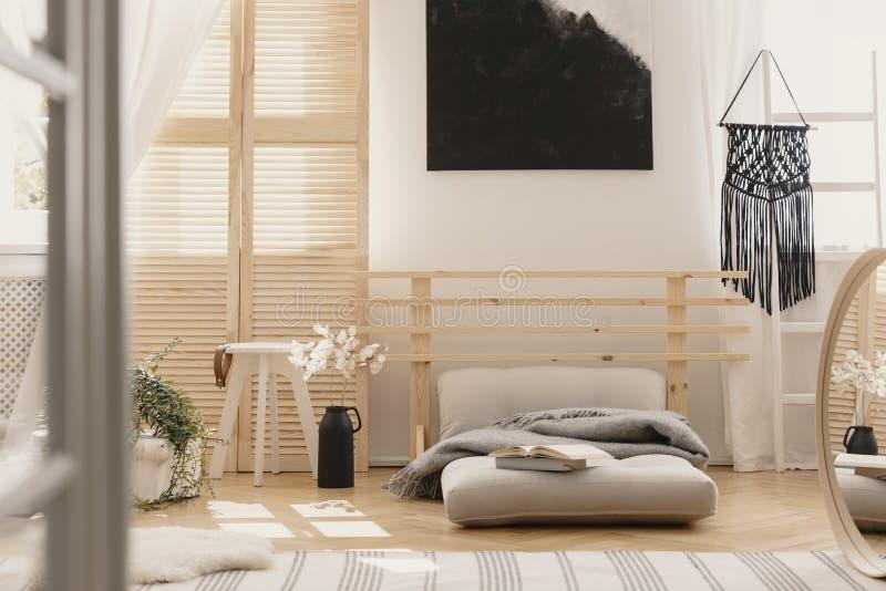 O macramê feito a mão preto na escada de madeira branca no quarto brilhante interior com mobília de madeira e o futon bege com ci imagens de stock