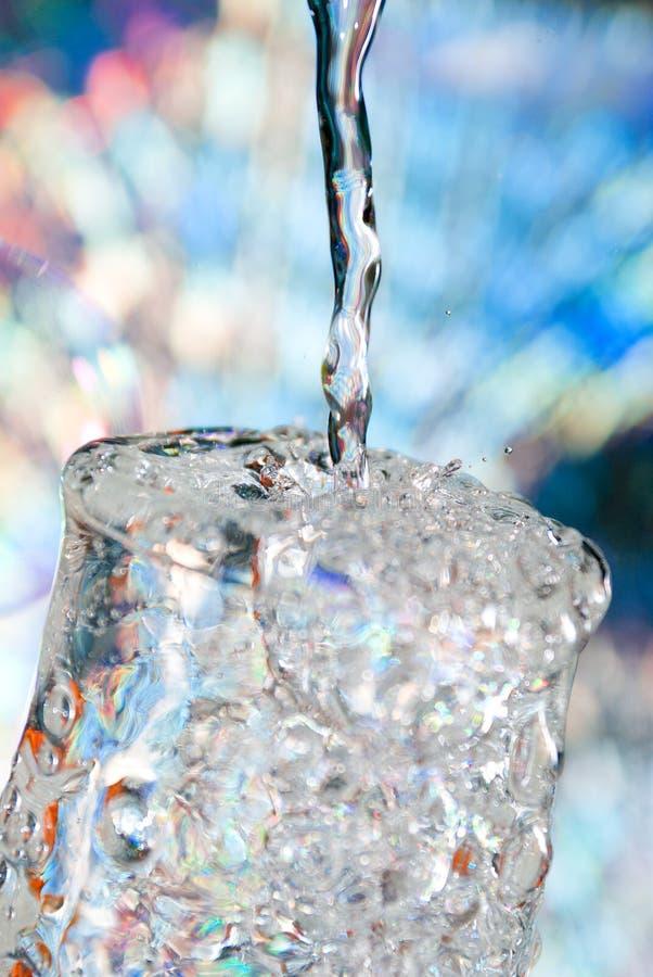 O macro da água derramou em um vidro da água fotos de stock