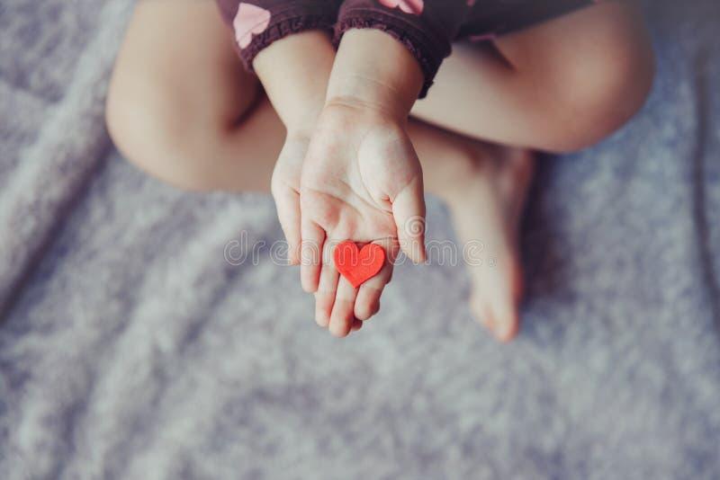 O macro da criança com pai adulto entrega as palmas que guardam um grupo de corações de papel vermelhos e roxos pequenos da espum imagem de stock