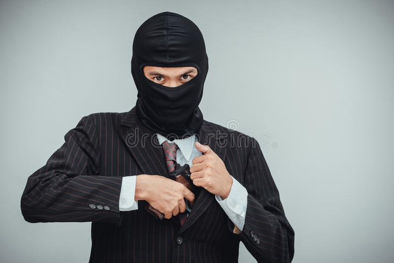 O Mafioso no terno retira uma arma antes do trabalho do roubo a um banco foto de stock royalty free