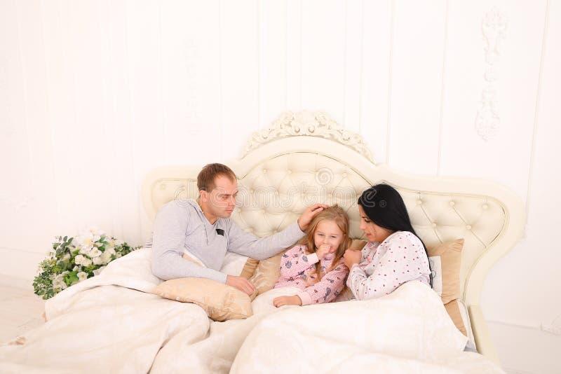 O mal do bebê, mãe limpa o ranho na cama imagens de stock