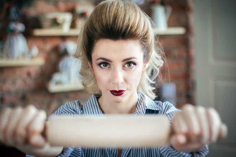 O mal 'sexy' da dona de casa da menina está olhando a câmera e está guardando um pino do rolo na frente da câmera no close up da  foto de stock
