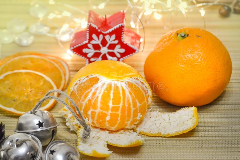 O mandarino e fatias alaranjadas secadas, sinos de Natal, uma vela, uma composição do Natal da festão fotografia de stock
