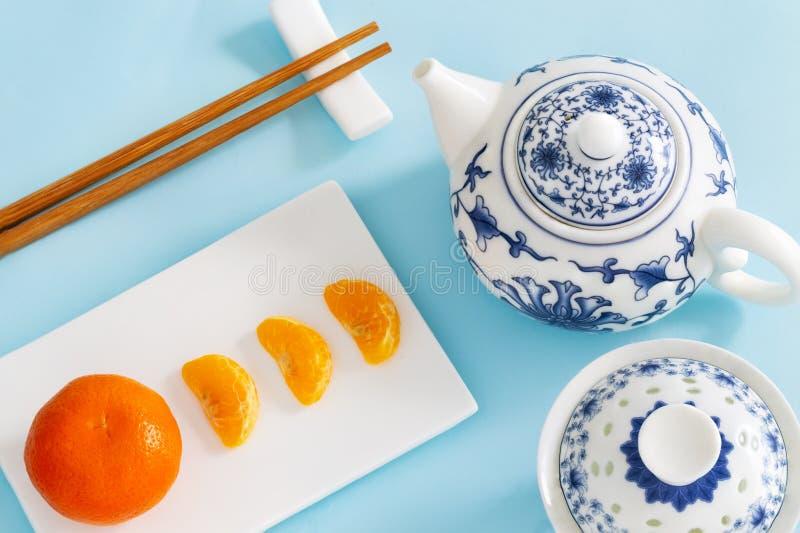 O mandarino, tangerina, ou clementina com segmentos ou fatias descascadas na placa do retângulo com a bacia chinesa do chá, poten foto de stock