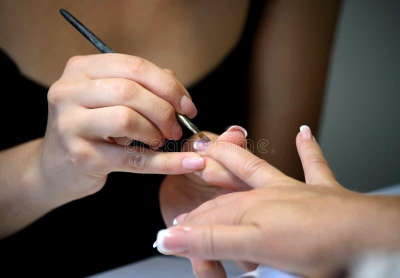 O Manicure que faz a fêmea entrega a coberta do esmalte imagem de stock royalty free