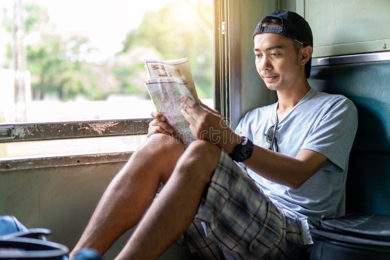 O mapa de viagem da leitura do mochileiro do homem asiático senta-se no assento velho do trem imagens de stock royalty free