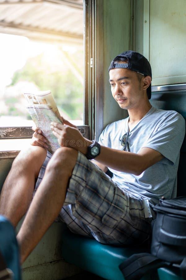 O mapa de viagem da leitura do mochileiro do homem asiático senta-se no trem velho imagem de stock royalty free