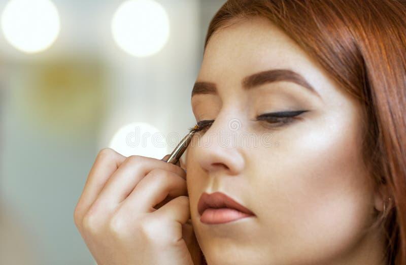O maquilhador aplica a composição e faz o forro do olho com uma escova profissional em um salão de beleza fotografia de stock royalty free