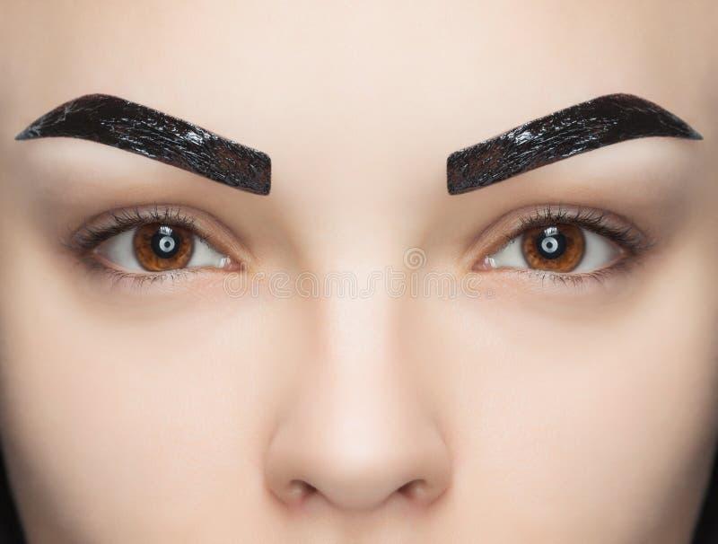 O maquilhador aplica a hena da pintura nas sobrancelhas em um salão de beleza fotos de stock royalty free