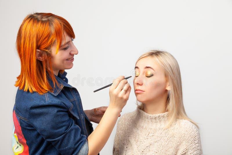 O maquilhador aplica uma composição a uma menina loura com uma escova em sua mão e em pôr sombras douradas às pálpebras fechados  imagens de stock