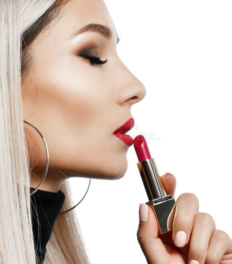 O maquilhador da mulher da composição do estilo do compartimento mantém o vermelho vermelho do batom isolado no branco imagens de stock