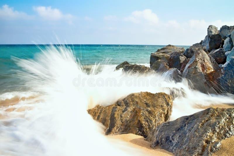 O mar acena batendo a praia rochosa em Malgrat de março, Espanha imagem de stock