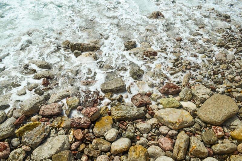 O mar acena, espuma do mar, quebra acima nas pedras litorais imagem de stock