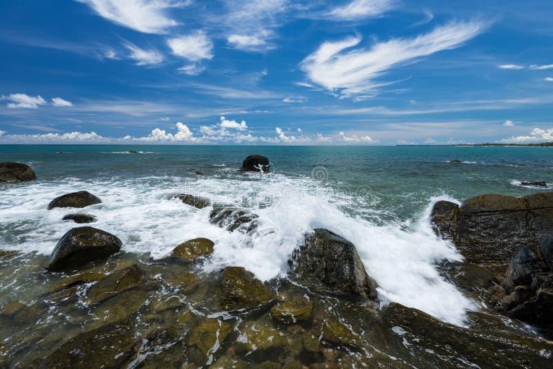 O mar acena a linha rocha do chicote do impacto na praia sob o céu azul imagem de stock