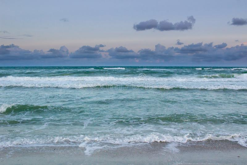 O mar acena o rolamento no Sandy Beach vazio, nascer do sol nebuloso tormentoso fotografia de stock royalty free