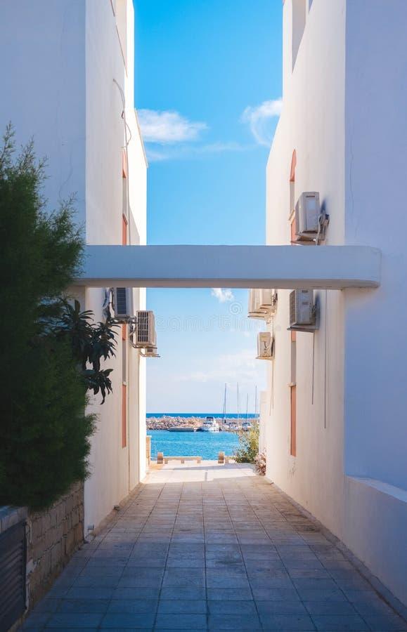 O mar através de duas construções brancas fotografia de stock royalty free