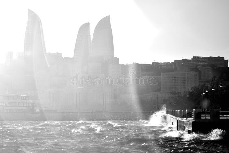 O mar Cáspio tormentoso com as ondas que quebram contra o Bulvar, com o alargamento sobre a chama eleva-se no fundo imagens de stock