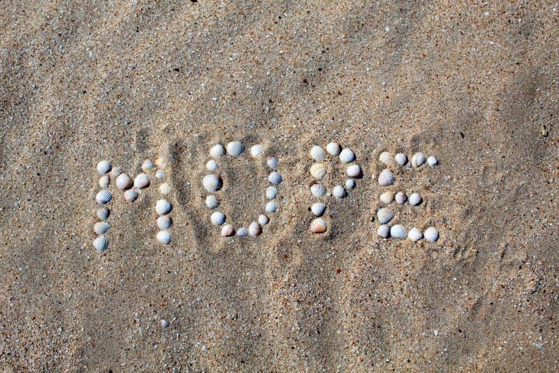 O mar da palavra, no russo, é apresentado na areia com escudos imagem de stock royalty free