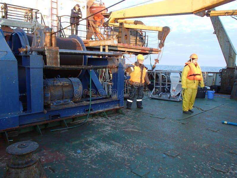 O mar de Okhotsk/Rússia - 17 de julho de 2015: Equipe da expedição da ciência perto do guincho na proa do levantamento do rv Akad foto de stock