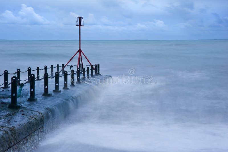 O mar dramático flui sobre o groyne na praia imagens de stock royalty free