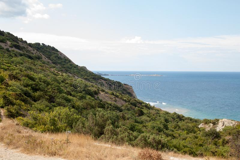 O mar em uma área montanhosa com as árvores na tarde imagens de stock