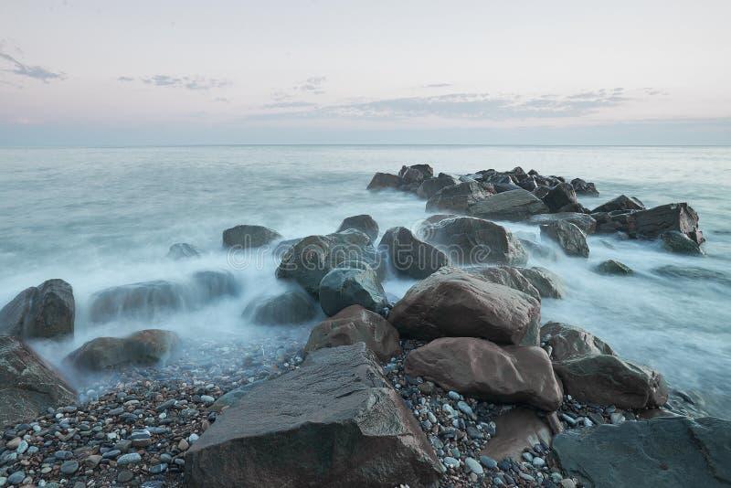 O mar lava as pedras grandes contra o por do sol cor-de-rosa A técnica usou - a exposição longa fotos de stock