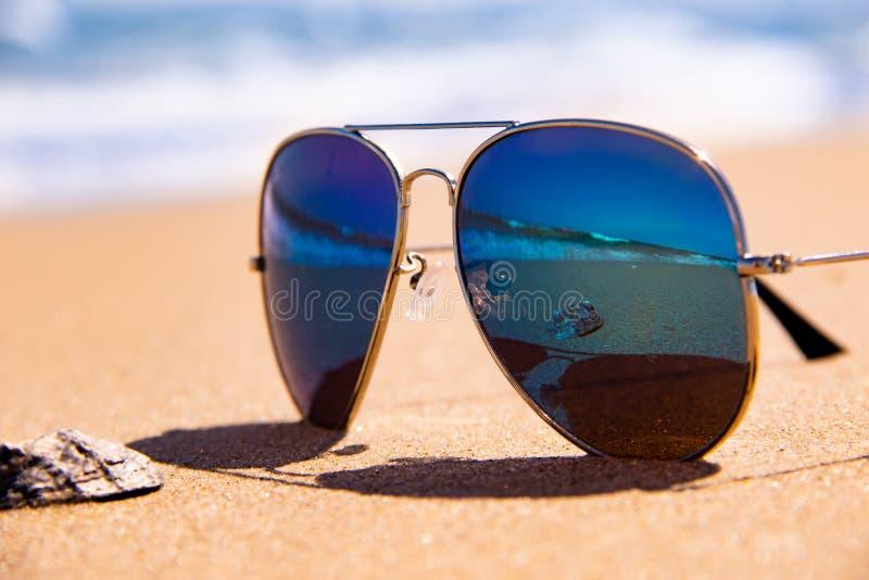 O mar tormentoso e o shell são refletidos nos óculos de sol do espelho no oceano tropical da praia no fundo foto de stock