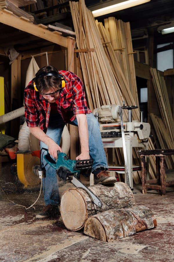 O marceneiro na oficina vê a árvore com uma serra de cadeia elétrica carpinteiro em processo do sawing imagens de stock royalty free