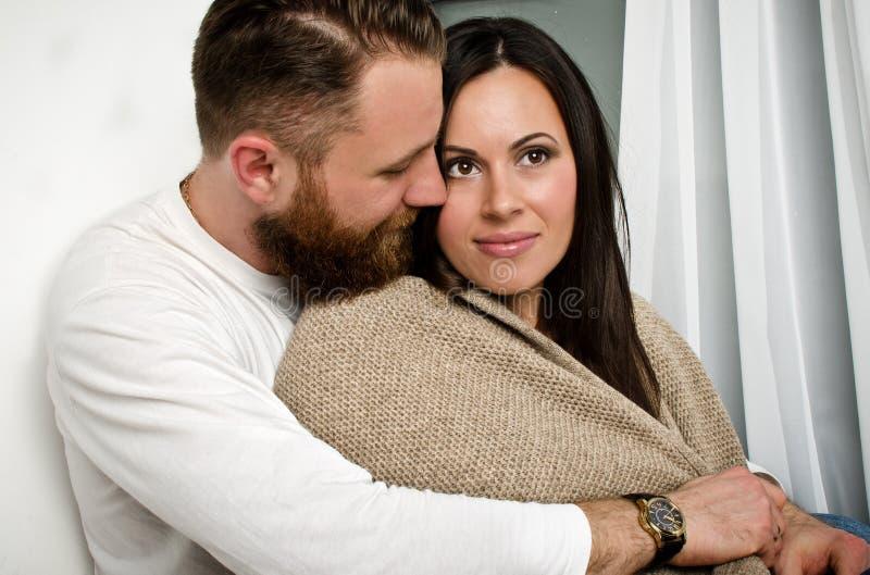 O marido abraça sua esposa e cobertura da proteção imagens de stock royalty free