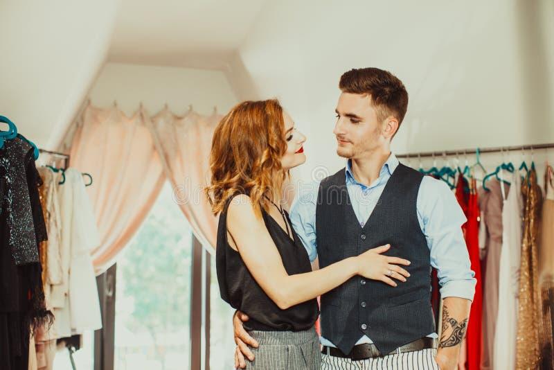 O marido ajuda a escolher o vestido para sua esposa imagens de stock royalty free