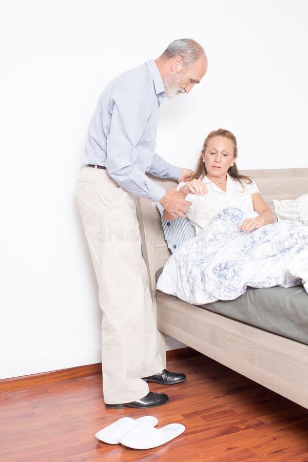 O marido ajuda a esposa a sair da cama fotos de stock