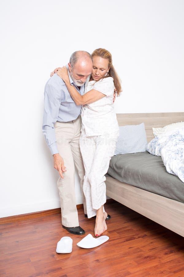 O marido ajuda a esposa a sair da cama imagem de stock