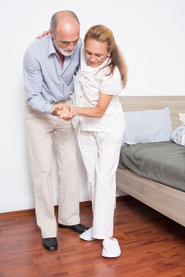 O marido ajuda a esposa a sair da cama fotografia de stock royalty free