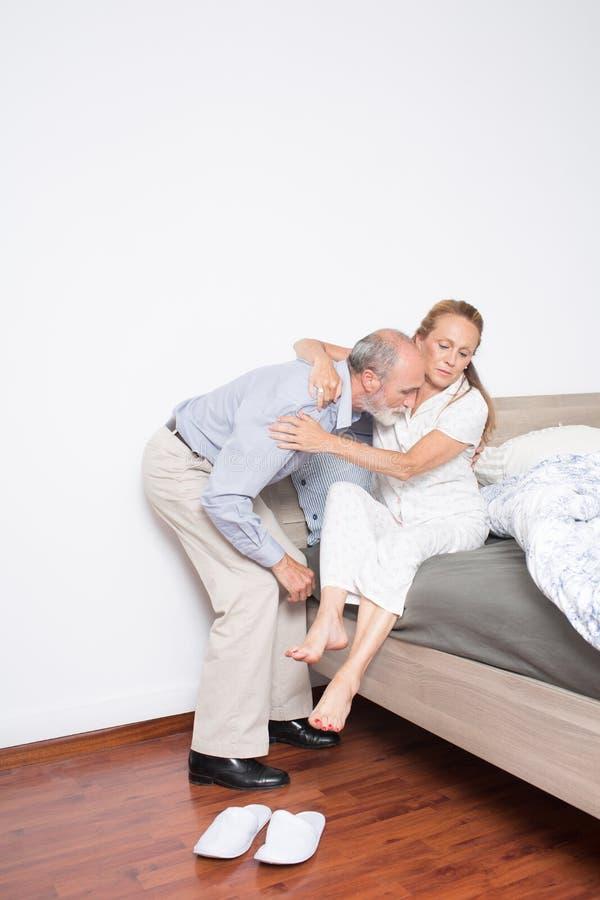 O marido ajuda a esposa a sair da cama foto de stock royalty free